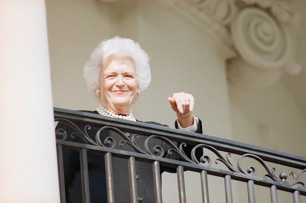 . First lady Barbara Bush points towards the White House balcony where she was waiting for her husband as he returned home from a day trip from Columbia, S.C., Feb. 15, 1989 Bush addressed a joint session of the South Carolina state legislature. (AP Photo/Charles Tasnadi)