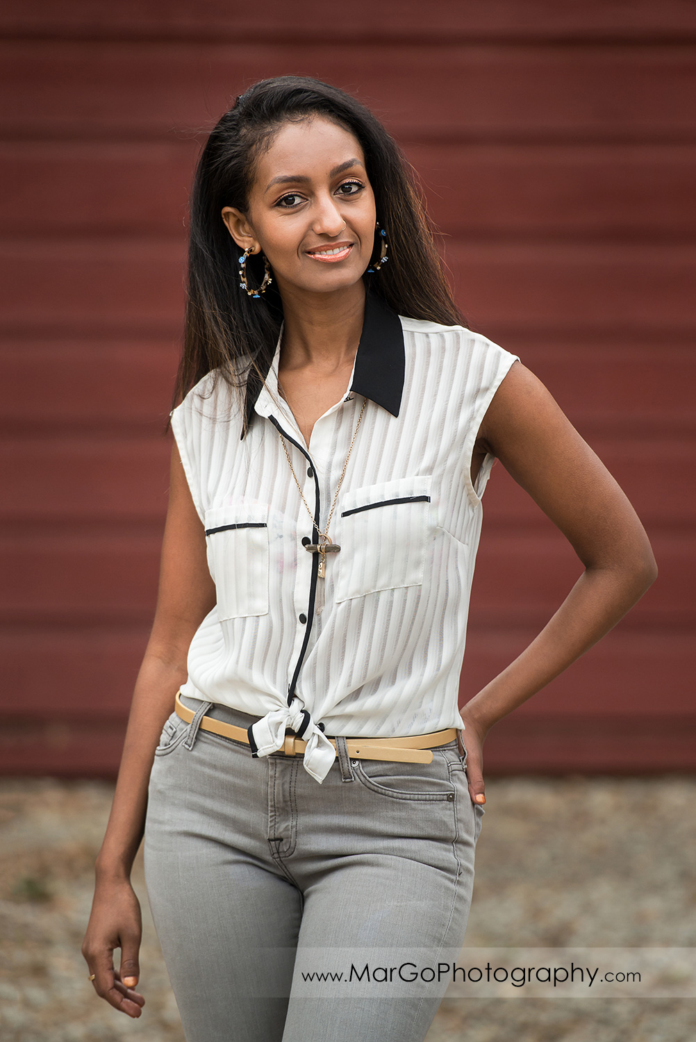 3/4 pose portrait of woman in white shirt and gray jeans standing in front of the red wooden barn in Shinn Historical Park and Arboretum in Fremont