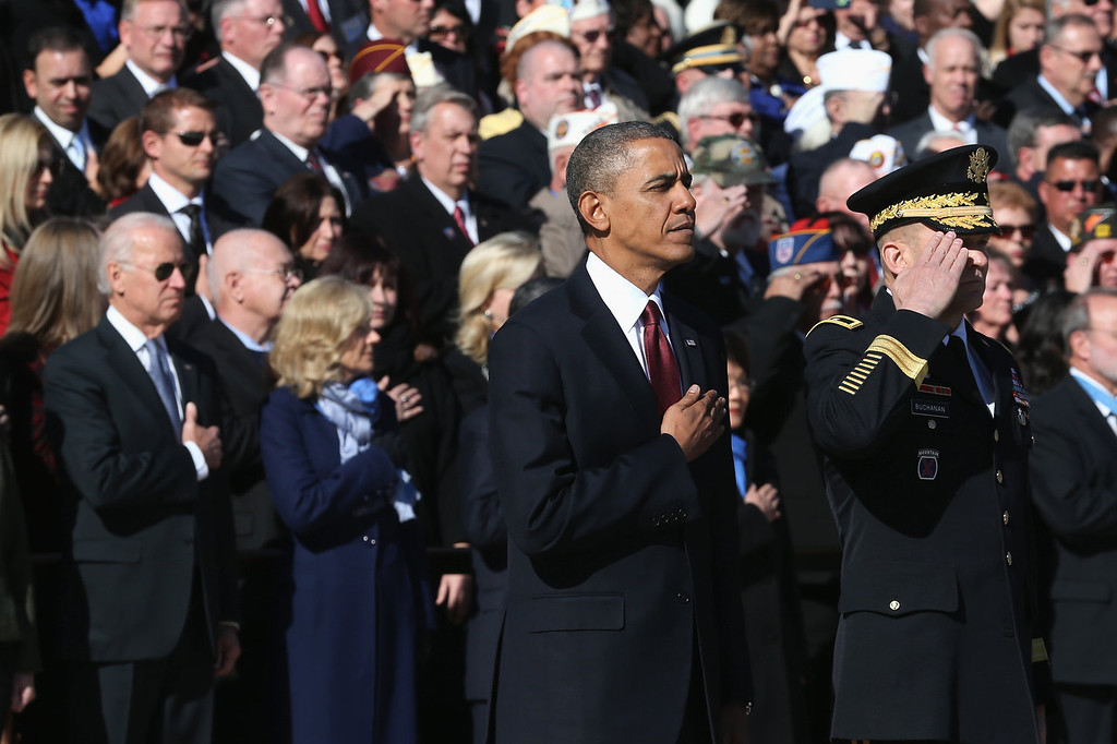 . U.S. President Barack Obama (C) looks on during a ceremony on Veterans Day at the Tomb of the Unknowns at Arlington National Cemetery on November 11, 2013 in Arlington, Virginia. For Veterans Day, President Obama is paying tribute to military veterans past and present who have served and sacrificed their lives for their country.  (Photo by Mark Wilson/Getty Images)