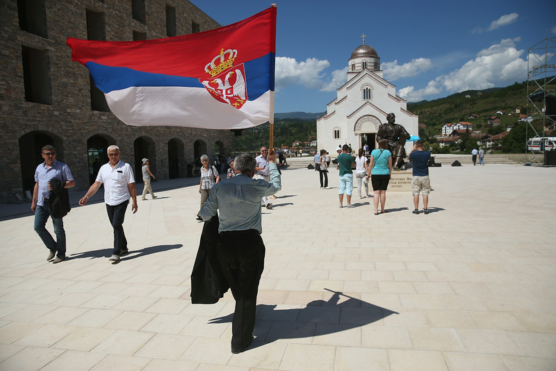 . A man waves a Serbian flag as he walks through the mock-village of Andricgrad on St. Vitus Day in Srpska Republika on June 28, 2014 in Visegrad, Bosnia and Herzegovina. Serbian leaders are scheduled to hold ceremonies at Andricgrad later in the day to mark the centenary of the assassination of Austrian Archduke Franz Ferdinand on June 28, 1914, by Serbian secessionist Gavrilo Princip, an event that propelled Europe into World War I. The city of Sarajevo is holding its own commemoration, though Serbian leaders are boycotting the Sarajevo events, claiming the Bosniaks have turned the commemoration too partisan. Andricgrad was built by Serbian film director Emir Kusturica and will become the set for a film about Yugoslav poet Ivo Andric.   (Photo by Sean Gallup/Getty Images)