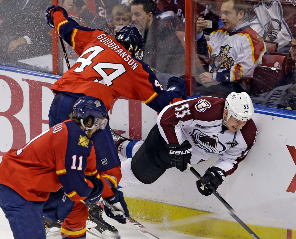 . Colorado Avalanche left wing Cody McLeod (55) goes down after being checked by Florida Panthers defenseman Erik Gudbranson (44) during the third period of an NHL hockey game in Sunrise, Fla., Friday, Jan. 24, 2014. The Avalanche won 3-2. (AP Photo/Alan Diaz)