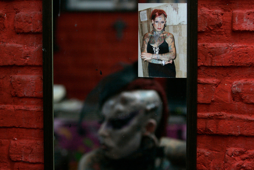 . An earlier photograph of Maria Jose Cristerna is seen as she is reflected in a mirror in her tattoo parlour and boutique in Guadalajara February 4, 2012. REUTERS/Alejandro Acosta