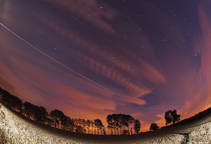 Aug 16 2011. 2149hrs super bright pass of the ISS. Looked stunning through the twilight blue skies and sporadic cloud cover. I used the corn field as a nice neutral colour foreground subject, lit with few bursts of flash. The line of trees were carefully chosen :-) Captured with Olympus E5 & 8mm fisheye.