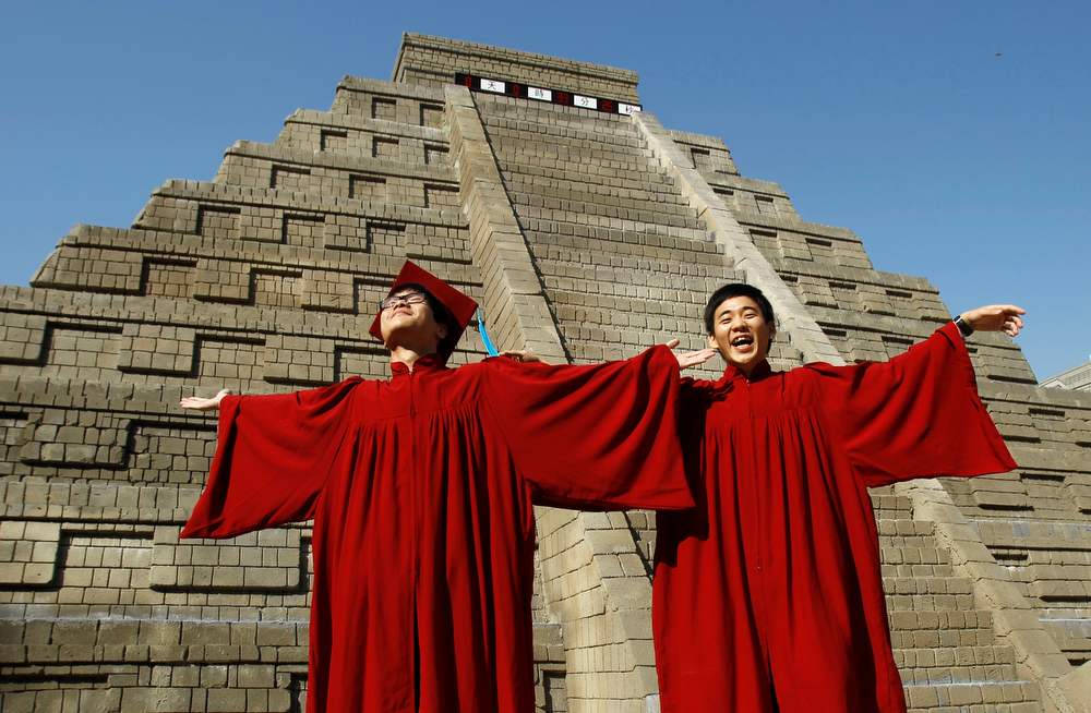 . Students dressed in graduation gowns pose in front of a mock pyramid moments before the countdown time when many believe the Mayan people predicted the end of the world, Friday, Dec. 21, 2012, in Taichung, southern Taiwan. (AP Photo/Wally Santana)