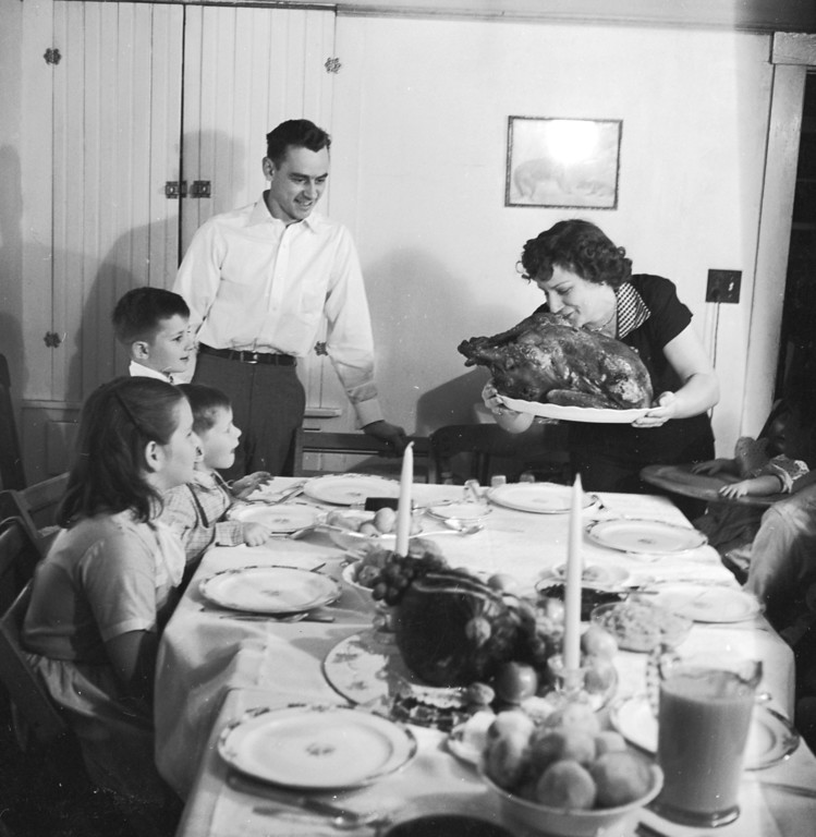 . circa 1955:  A Thanksgiving turkey comes to the table watched by the family.  (Photo by Evans/Three Lions/Getty Images)