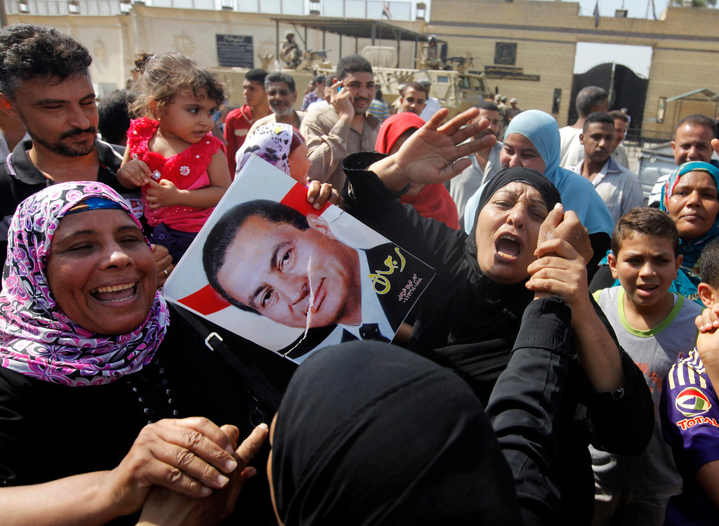 ". Supporters of Egypt\'s deposed autocrat Hosni Mubarak hold a poster of him and chant slogans in front of Torah Prison where he has been held, in Cairo, Egypt, Thursday, Aug. 22, 2013. The Arabic writing on the poster reads ""men of Mubarak.\"" Egypt\'s ousted leader Hosni Mubarak, wearing a white shirt and loafers while flashing a smile, was released from prison Thursday and transported to a military hospital in a Cairo suburb where he will be held under house arrest. (AP Photo/Amr Nabil)"