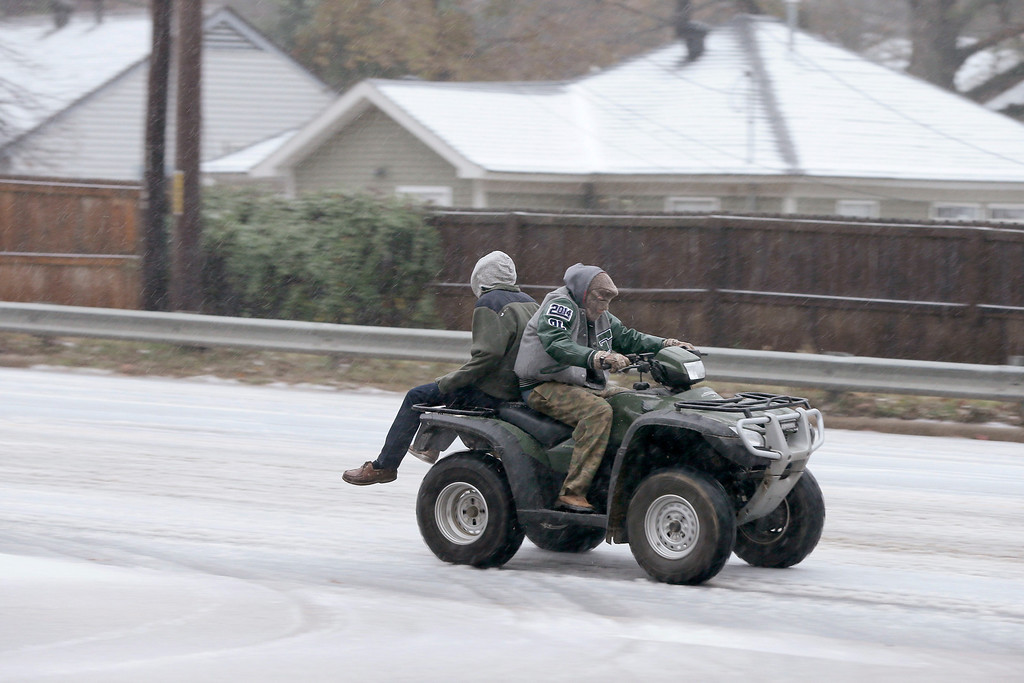 . Two people ride a all terrain vehicle on a sleet-covered street in Little Rock, Ark., Friday, Dec. 6, 2013. Weather forecasters lifted an ice storm warning Friday for much of central Arkansas. (AP Photo/Danny Johnston)