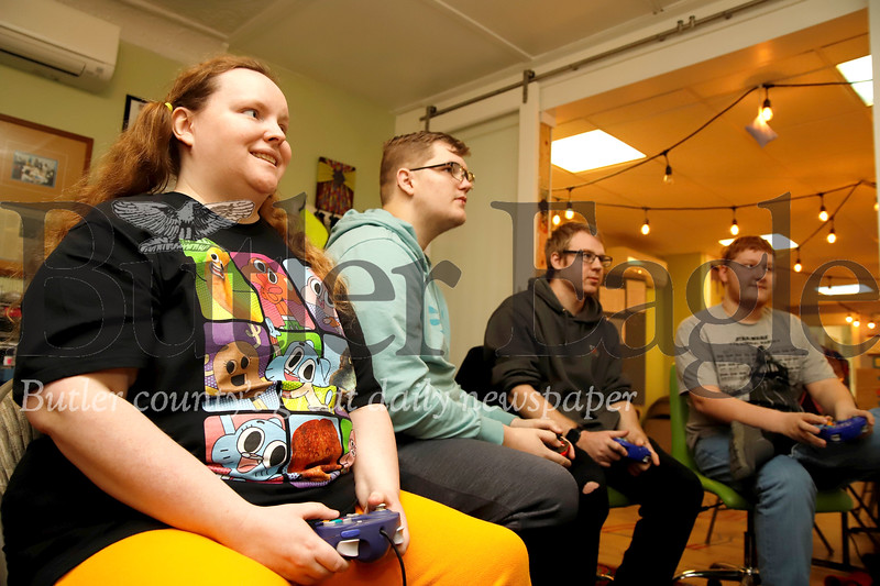Kim Bingham (left), Ryan Kish, Stephen Matousek and Aaron Bennett compete in a round of Smash Brothers at Parents in Toto's community center game day Saturday. The Zelienople-based non-profit offers a community center and resources for teens and young adults with Autism and their families. Seb Foltz/Butler
