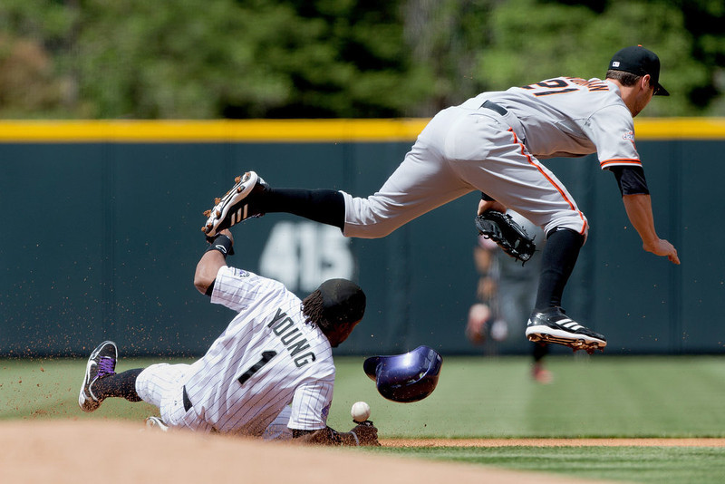 . Eric Young Jr. #1 of the Colorado Rockies slides in safely for a stolen base and takes out second baseman Nick Noonan #21 of the San Francisco Giants during the first inning at Coors Field on May 19, 2013 in Denver, Colorado.  (Photo by Justin Edmonds/Getty Images)