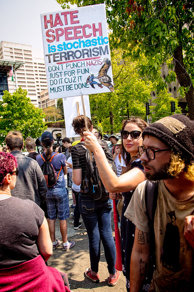 """A young woman holds up her sign, """"HATE SPEECH is stochastic TERRORISM. DON'T PUNCH NAZIS JUST FOR FUN, DO IT CUZ IT MUST BE DONE."""""""