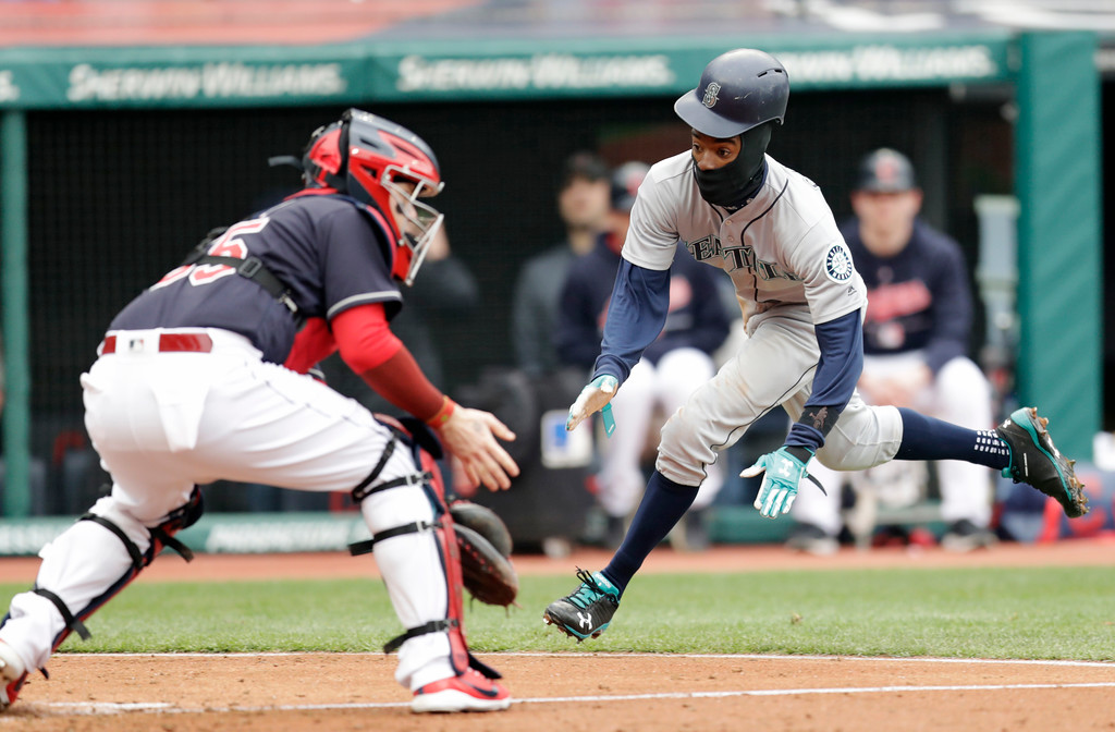 . Seattle Mariners\' Dee Gordon slides into home plate as Cleveland Indians\' Roberto Perez waits for the ball in the fourth inning of a baseball game, Saturday, April 28, 2018, in Cleveland. Gordon was safe. (AP Photo/Tony Dejak)