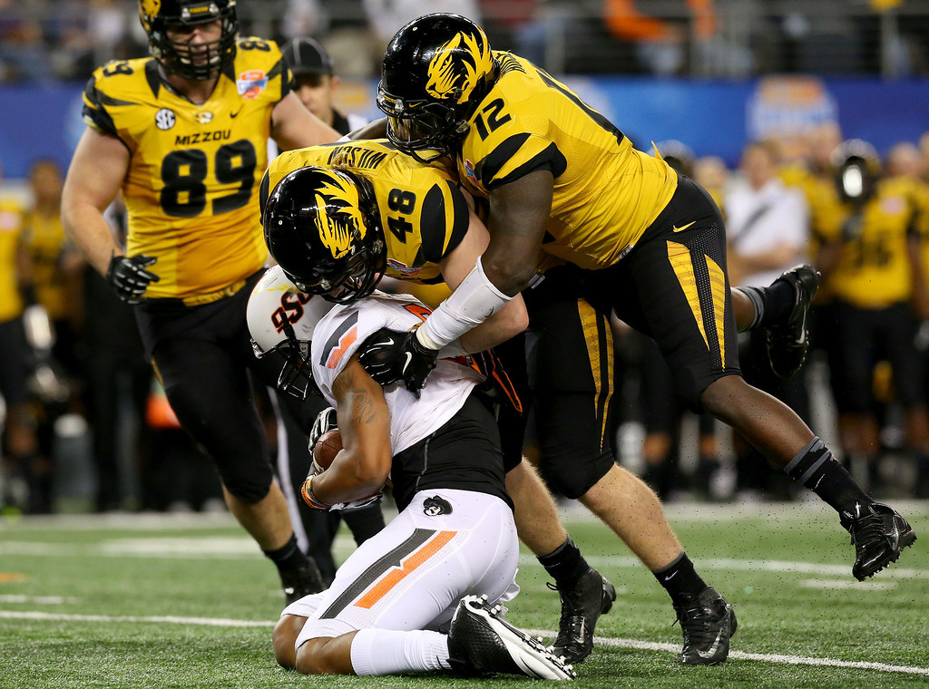 . ARLINGTON, TX - JANUARY 03:  Tracy Moore #87 of the Oklahoma State Cowboys is tackled by Darvin Ruise #12 and Kony Ealy #47 of the Missouri Tigers in the third quarter during the AT&T Cotton Bowl on January 3, 2014 in Arlington, Texas.  (Photo by Ronald Martinez/Getty Images)