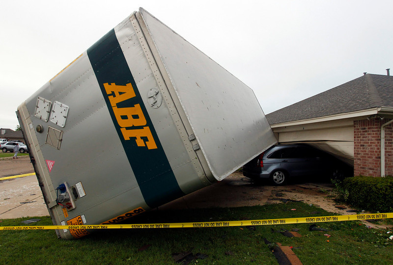 . A trailer blown into a home on Lindsay Lane in Cleburne rests on a car after a tornado touch down in Cleburne, Texas May 16, 2013. At least six people were killed and seven were missing after as many as 10 tornadoes ripped through north-central Texas Wednesday evening, leaving a trail of destruction from the worst severe storm outbreak in the United States so far this year.  REUTERS/Richard Rodriguez