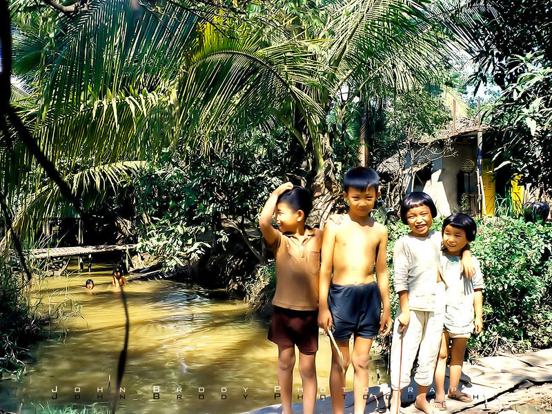 Sweet Vietnamese Kids in front of their pool / bathtub / water supply / kitchen sink. Conditions were hard for those kids but it didn't seem to phase them. - JohnBrody.com