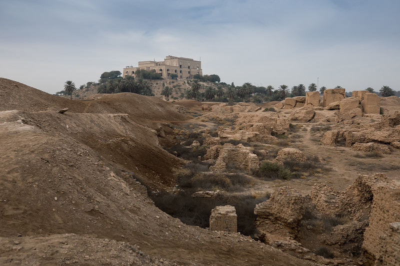Looking over to the former Summer Palace of Saddam Husseim with the original ruins of Babylon in the foreground. Following the 2003 American invasion, US camp Alpha was set up partially on the ruins. Significant damage occurred with areas leveled to create landing pads for helicopters and parking lots for vehicles, tanks rumbled over ancient bricks, Polish troops dug trenches through a ancient temple and soil holding artifacts and bones was scooped into sandbags.