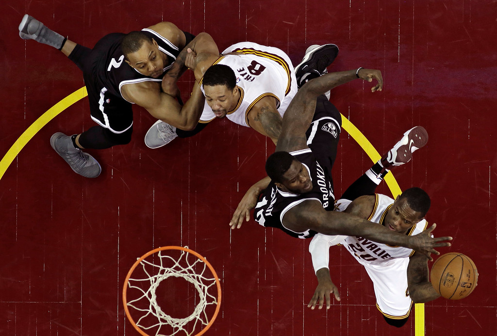 . Cleveland Cavaliers\' Kay Felder, right, shoots under pressure from Brooklyn Nets\' Anthony Bennett, second from right, in the second half of an NBA basketball game, Friday, Dec. 23, 2016, in Cleveland. Nets\' Randy Foye, left, and Cavaliers\' Channing Frye watch. (AP Photo/Tony Dejak)
