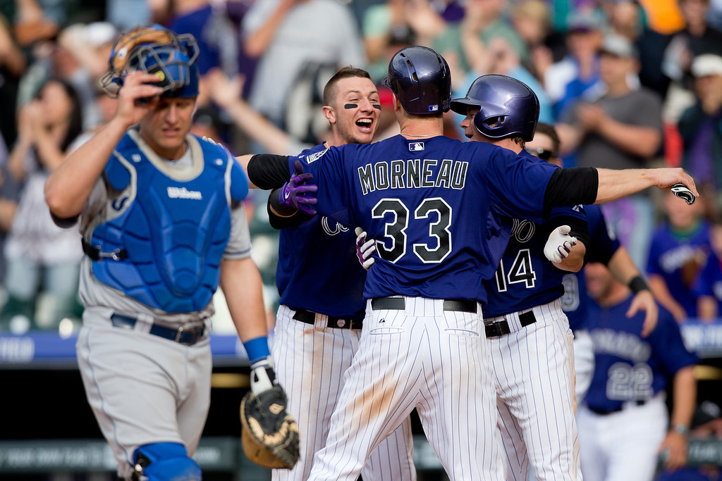 . DENVER, CO - JUNE 7:  Justin Morneau #33 of the Colorado Rockies celebrates with Troy Tulowitzki #2 and Josh Rutledge #14 after scoring the winning run in the 10th inning on a triple by Brandon Barnes (not pictured) as catcher Tim Federowicz #26 of the Los Angeles Dodgers walks off the field at Coors Field on June 7, 2014 in Denver, Colorado. The Rockies defeated the Dodgers 5-4 in 10 innings to end their eight game losing streak. (Photo by Justin Edmonds/Getty Images)