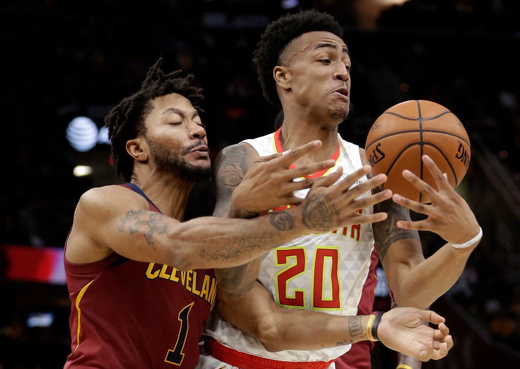. Atlanta Hawks\' John Collins (20) and Cleveland Cavaliers\' Derrick Rose (1) battle for the ball in the first half of an NBA basketball game Sunday, Nov. 5, 2017, in Cleveland. (AP Photo/Tony Dejak)
