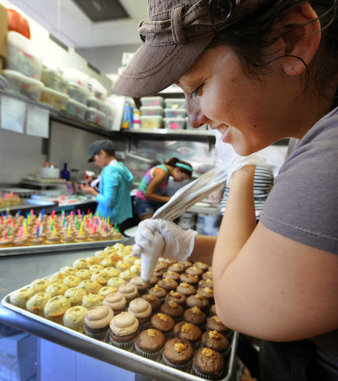 """. Dana Flamingo puting on sugar coating on cupcakes at The Cake Mamas in Glendora.  The Cake Mamas gave away 1,000 free cupcakes from 10 a.m. to 7:00 p.m. celebrating three years in businessTuesday, October 1, 2013. The Cake Mamas won the Food Network \""""Cupcake Wars\"""" in 2011.(Photos by Walt Mancini/Pasadena Star-News)"""