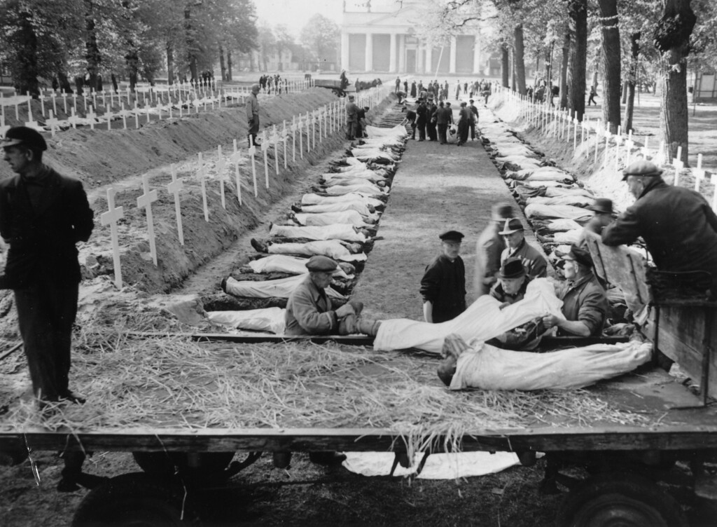 . 7th May 1945:  German civilians at Ludwiglust, Germany prepare for burial, some of the 200 victims of starvation in the Nazi concentration camp near Wobbelin. The bodies were brought from the camp on the back of a lorry seen in the foreground.  (Photo by Keystone/Getty Images)