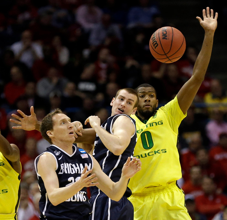 . BYU guard Skyler Halford, left, BYU forward Josh Sharp, and Oregon forward Mike Moser chase after a loose ball during the first half of a second-round game in the NCAA college basketball tournament Thursday, March 20, 2014, in Milwaukee. (AP Photo/Jeffrey Phelps)