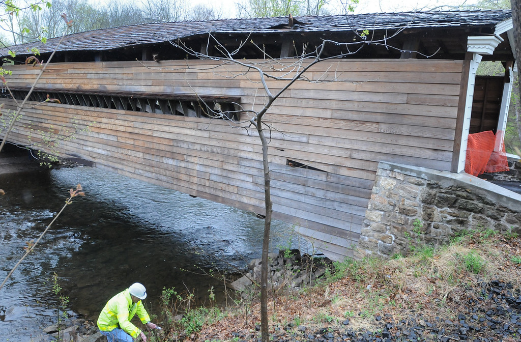 . Officials inspect the Rapps Dam Bridge in East Pikeland Township Tuesday afternoon after the operator of a tractor trailer drove his truck through the covered bridge causing structural damage to beams and the roof. Photo by John Strickler The Mercury