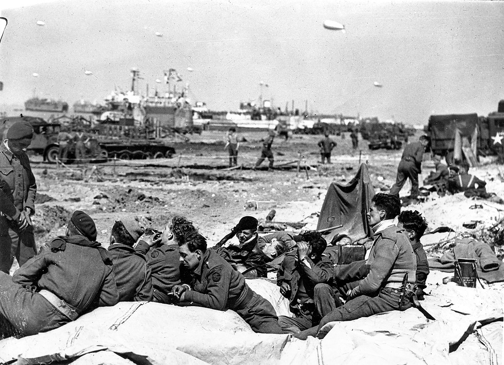 Description of . Commandos of the British Army rest on the beach after D-Day at Normandy, France, on June 7, 1944.  (AP Photo)