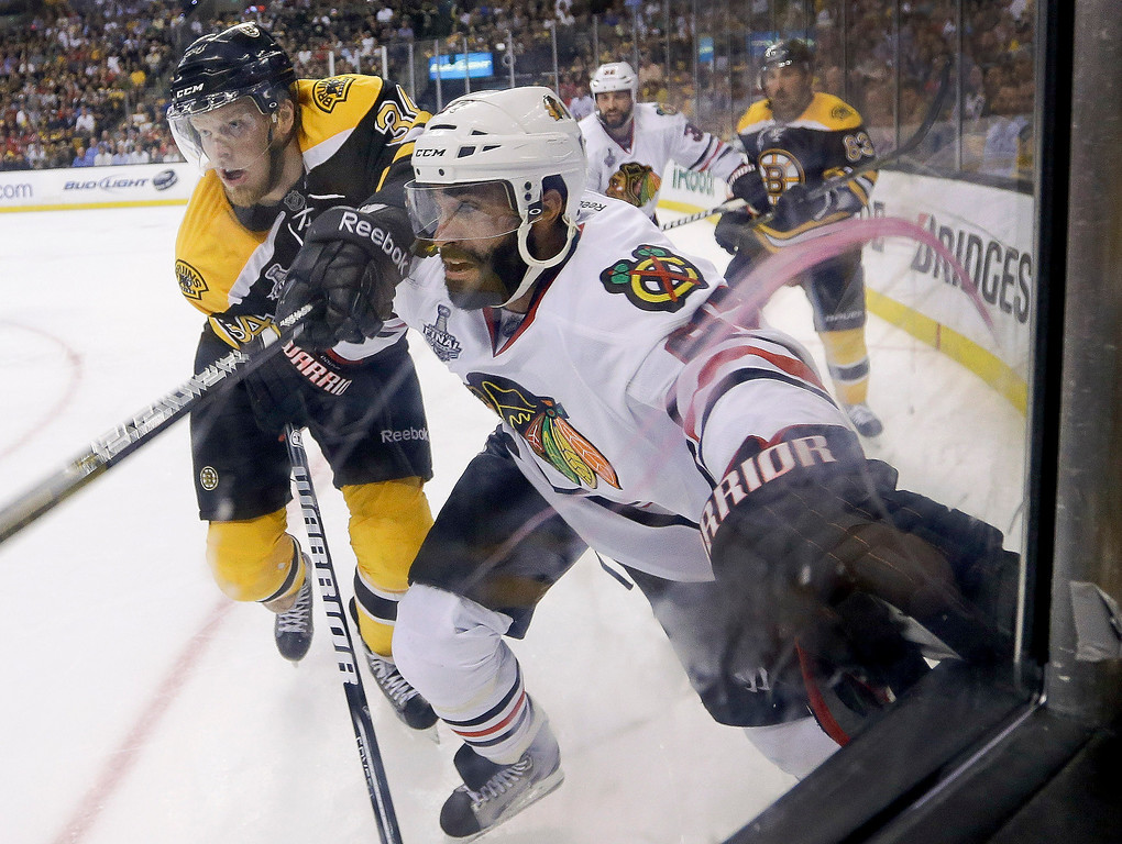 . Boston Bruins center Carl Soderberg (34), of Sweden, and Chicago Blackhawks defenseman Johnny Oduya (27), of Sweden, fight for position along the boards during the second period in Game 6 of the NHL hockey Stanley Cup Finals Monday, June 24, 2013 in Boston. (AP Photo/Elise Amendola)