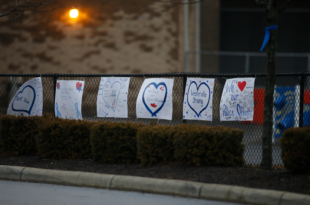 . Signs of support are seen outside of St. Paul the Apostle Catholic Church in Westerville, Ohio, before funeral services for Westerville police officers Anthony Morelli and Eric Joering Friday, Feb. 16, 2018. The two veteran officers were shot after entering a residence Saturday February, 10, 2018. The officers returned fire, wounding 30-year-old Quentin Smith, who has been charged with aggravated murder and remains hospitalized. (AP Photo/Paul Vernon)