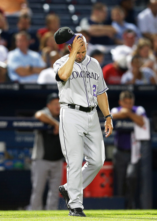 . Colorado Rockies manager Walt Weiss (22) scratches his head as he walks to the mound to pull relief pitcher Edgmer Escalona in the eighth inning of a baseball game against the Atlanta Braves in Atlanta, Thursday, Aug. 1, 2013. Atlanta won 11-2. (AP Photo/John Bazemore)