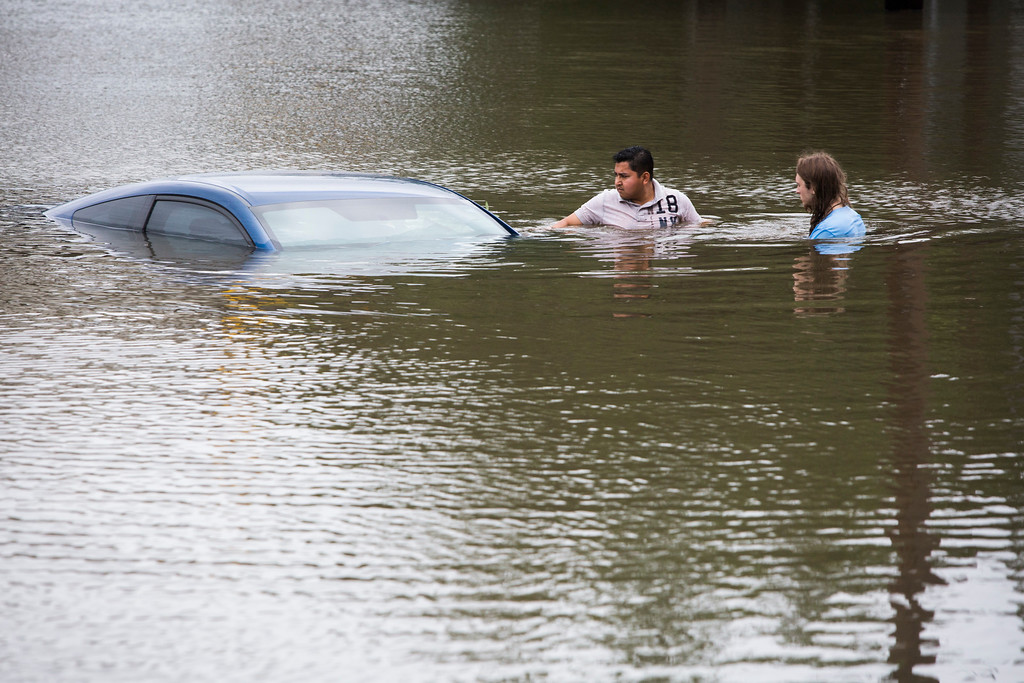 . Roberto Salas, left, and Lewis Sternhagen check a flooded car on the frontage road between South Loop West Freeway and South Post Oak Road near the Willow Waterhole Bayou, Tuesday, May 26, 2015, in Houston. Floodwaters kept rising Tuesday across much of Texas as storms dumped almost another foot of rain on the Houston area, stranding hundreds of motorists and inundating the highways. (Marie D. De Jesus/Houston Chronicle via AP)