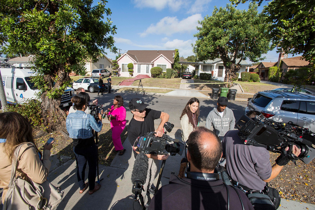 ". Neighbors are interviewed by media in front of the home of actor Michael Jace on Tuesday, May 20, 2014, in Los Angeles.  Jace, who played a police officer on the hit TV show ""The Shield,\"" was arrested on suspicion of homicide after his wife was found shot to death in their Los Angeles home, authorities said. Police arrived at the couple\'s home around 8:30 p.m. Monday after a report of shots fired, Officer Chris No said. April Jace, 40, was found dead inside, officials said.  Jace was taken into custody and booked early Tuesday on suspicion of homicide, No said. He was being held in a Los Angeles jail in lieu of $1 million bail.   (AP Photo/Ringo H.W. Chiu)"