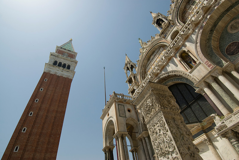 Looking up the facade of St. Mark's Basilica and bell tower at St. Mark's Square - Venice, Italy