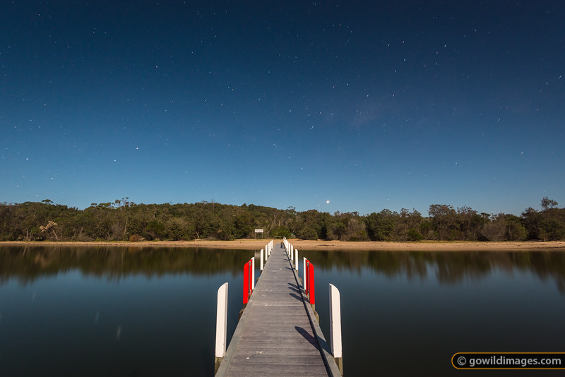 Sperm Whale Head jetty, Point Wilson, The Lakes NP. A long exposure under a full moon on a calm night. The planet Venus sets just above the trees at the start of the pier, with the Southern Cross just over the trees to the left.