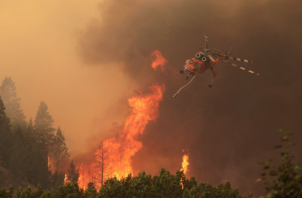 . Helicopters battle the 64,000 acre Beaver Creek Fire on Friday, Aug., 16, 2013 north of Hailey, Idaho. A number of residential neighborhoods have been evacuated because of the blaze.   (AP Photo/Times-News, Ashley Smith)
