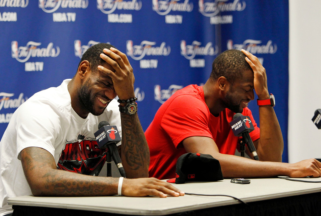 . Miami Heat\'s LeBron James, left, and Dwyane Wade share a laugh during a basketball news conference, Tuesday, June 14, 2011 in Miami. Instead of hosting Game 7 of the NBA finals on Tuesday, the Heat packed up their stuff for the summer. (AP Photo/Wilfredo Lee)