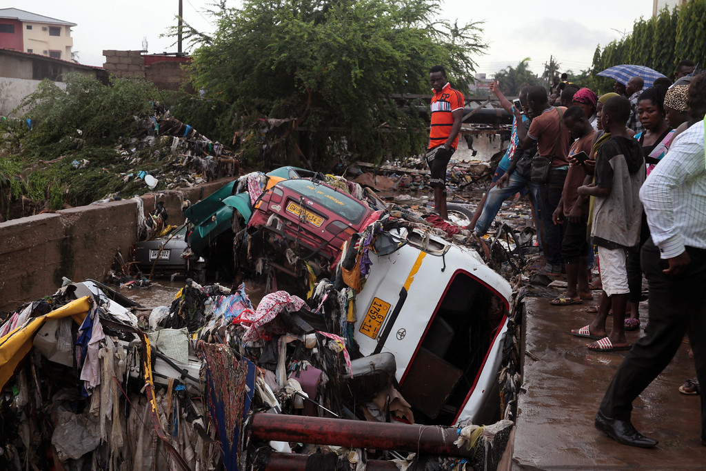 . Cars are piled up after being washed away after heavy rain near a gas station explosion in Accra, Ghana, Thursday, June 4, 2015. Flooding in Ghana\'s capital swept stored fuel into a nearby fire, setting off a huge explosion at a gas station that killed scores of people and set alight neighboring buildings, authorities said Thursday. (AP Photo/Christian Thompson)
