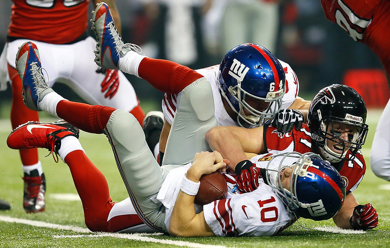 . Kroy Biermann #71 of the Atlanta Falcons sacks  Eli Manning #10 of the New York Giants at Georgia Dome on December 16, 2012 in Atlanta, Georgia.  (Photo by Kevin C. Cox/Getty Images)