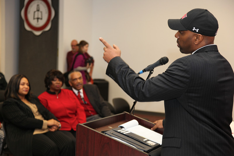 Ron Dickerson, Jr. who was named Gardner-Webb Head Football Coach makes a point while his father former NFL great Ron Dickerson, Sr. in the front row listens.