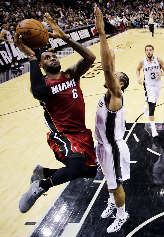 . Miami Heat forward LeBron James (6) shoots over San Antonio Spurs forward Kawhi Leonard (2) during the second half in Game 1 of the NBA basketball finals on Thursday, June 5, 2014 in San Antonio. (AP Photo/Eric Gay, Pool)