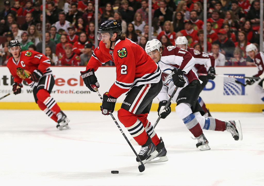 . CHICAGO, IL - DECEMBER 27: Duncan Keith #2 of the Chicago Blackhawks pushes the puck up the ice past P.A. Parenteau #15 of the Colorado Avalanche at the United Center on December 27, 2013 in Chicago, Illinois.   (Photo by Jonathan Daniel/Getty Images)