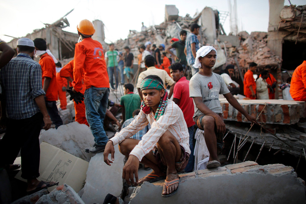 . A rescue worker takes a break as he tries to rescue garment workers trapped in the Rana Plaza building which collapsed, in Savar, 30 km (19 miles) outside Dhaka April 24, 2013.  REUTERS/Andrew Biraj