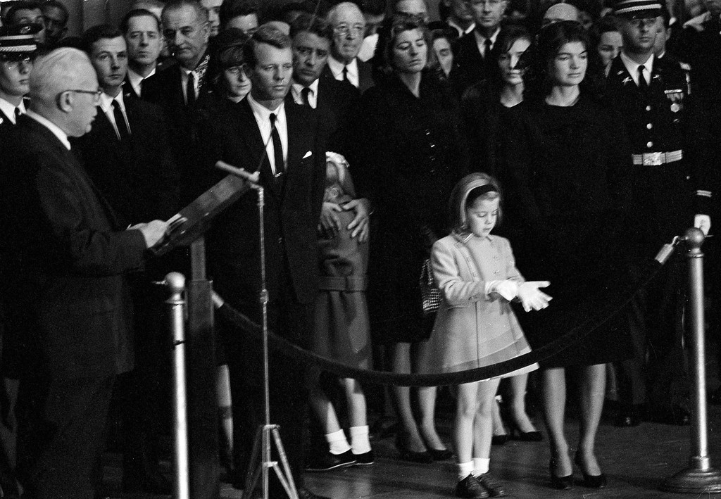 . Jacqueline Kennedy stands with daughter Caroline as Chief Justice Earl Warren eulogizes the slain president in the Capitol rotunda in Washington, Nov. 24, 1963. From left: soldier Stephen Smith, unidentified, President Lyndon B. Johnson, Patricia Kennedy Lawford, Attorney General Robert F. Kennedy, Peter Lawford comforting daughter Sydney and Mrs. Smith.   (AP Photo)