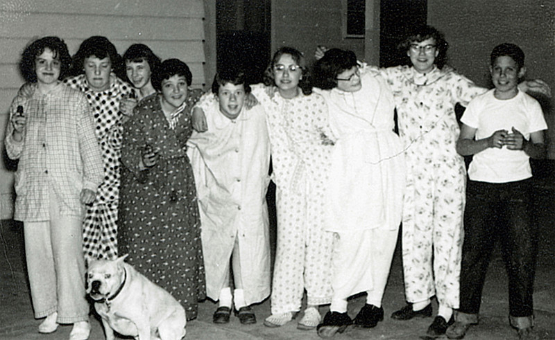 """1955? - Slumber party at Rebelsky's. Anita Harrison, ---, Connie Thiesen, Beth Rebelsky, Barbara Anderson, Connie Hebler, Mary McElrath, Carol Anderson, Steve Rebelsky. The white boxer is """"Pookie"""", Barbara Anderson's dog."""