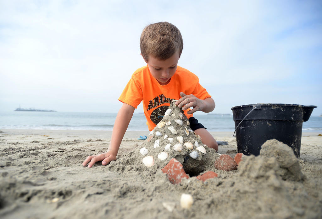 . Children had a chance to hone their sand castle building skills in a sand castle camp Monday at Granada Beach in Belmont Shore. Daniel Gates, 9, of Long Beach adds seashells found on the beach to his creation. 20130805 Photo by Steve McCrank / Staff Photographer
