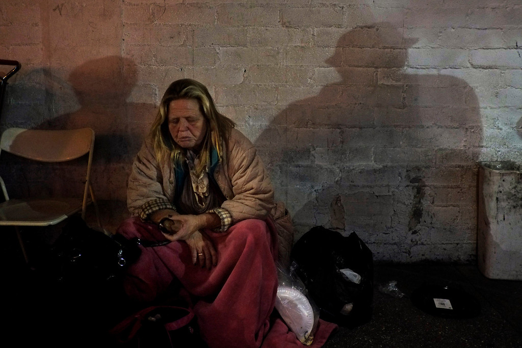 . A homeless woman eats a piece of fruit as two homeless men cast shadows on the wall in the Skid Row area of Los Angeles, Thursday, March 21, 2013. (AP Photo/Jae C. Hong)