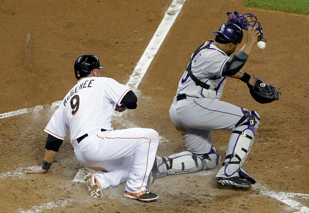 . Miami Marlins\' Casey McGehee (9) scores as Colorado Rockies catcher Wilin Rosario loses the ball in the third inning of a baseball game, Thursday, April 3, 2014, in Miami. (AP Photo/Lynne Sladky)