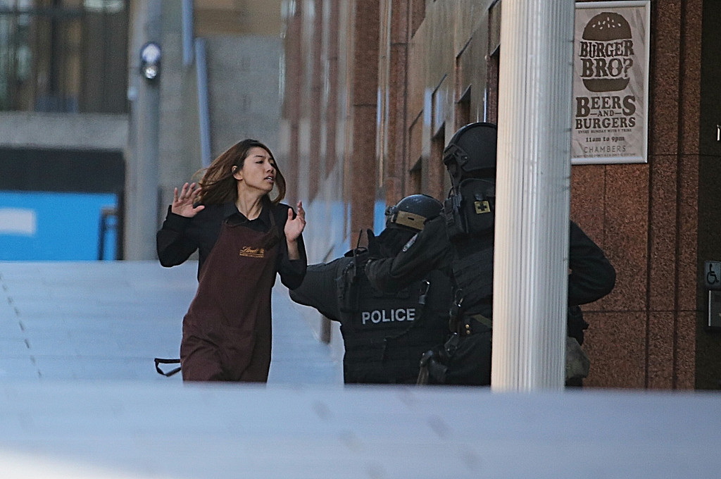 . An armed tactical response police officer grabs a hostage as she flees from a cafe under siege at Martin Place in the central business district of Sydney, Australia, Monday, Dec. 15, 2014. New South Wales state police would not say what was happening inside the cafe or whether hostages were being held. But television footage shot through the cafe\'s windows showed several people with their arms in the air. (AP Photo/Rob Griffith)