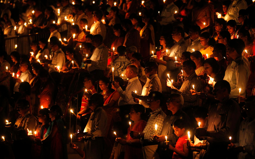 . Christians hold candles as they offer prayers to celebrate Easter outside a church in the western Indian city of Ahmedabad March 30, 2013. Holy Week is celebrated in many Christian traditions during the week before Easter. Picture taken March 30, 2013. REUTERS/Amit Dave