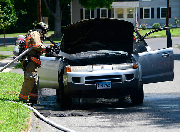 7/20/2018 Mike Orazzi | Staff A Bristol firefighter extinguishes a car fire in the engine compartment of a Saturn Vue on Driscoll Drive Friday afternoon. No injuries were reported.